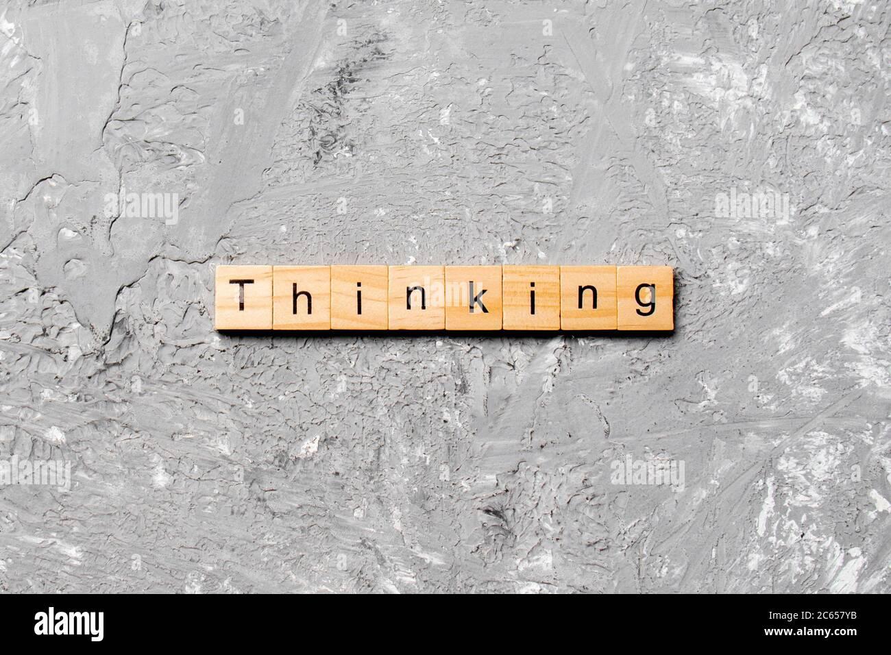 pensar palabra escrita en bloque de madera. pensar texto en tabla de cemento para su diseño, concepto. Foto de stock