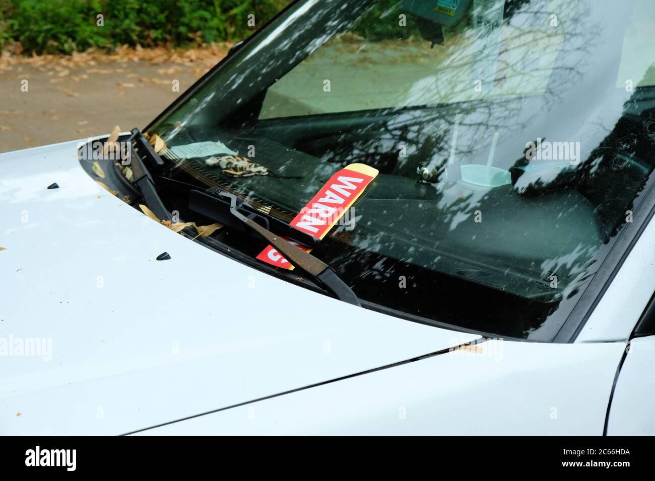 Aviso de boleto rojo de violación de estacionamiento en un parabrisas debajo de la escobilla del limpiaparabrisas de un auto blanco para vehículos de estacionamiento donde no está permitido; Portland, OR. Foto de stock