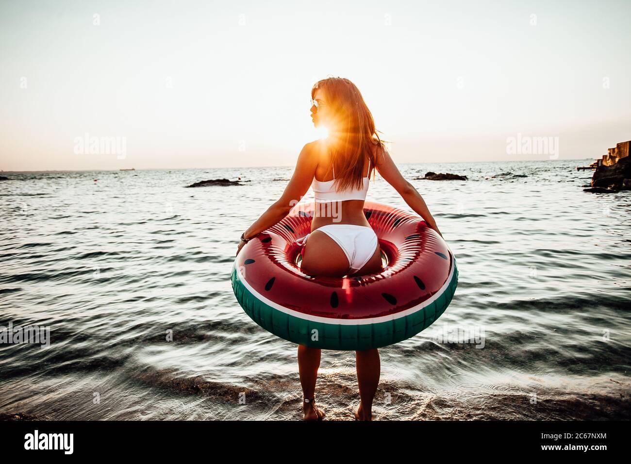 Chica divirtiéndose en la playa. Estilo de vida divertido en verano. Foto de stock