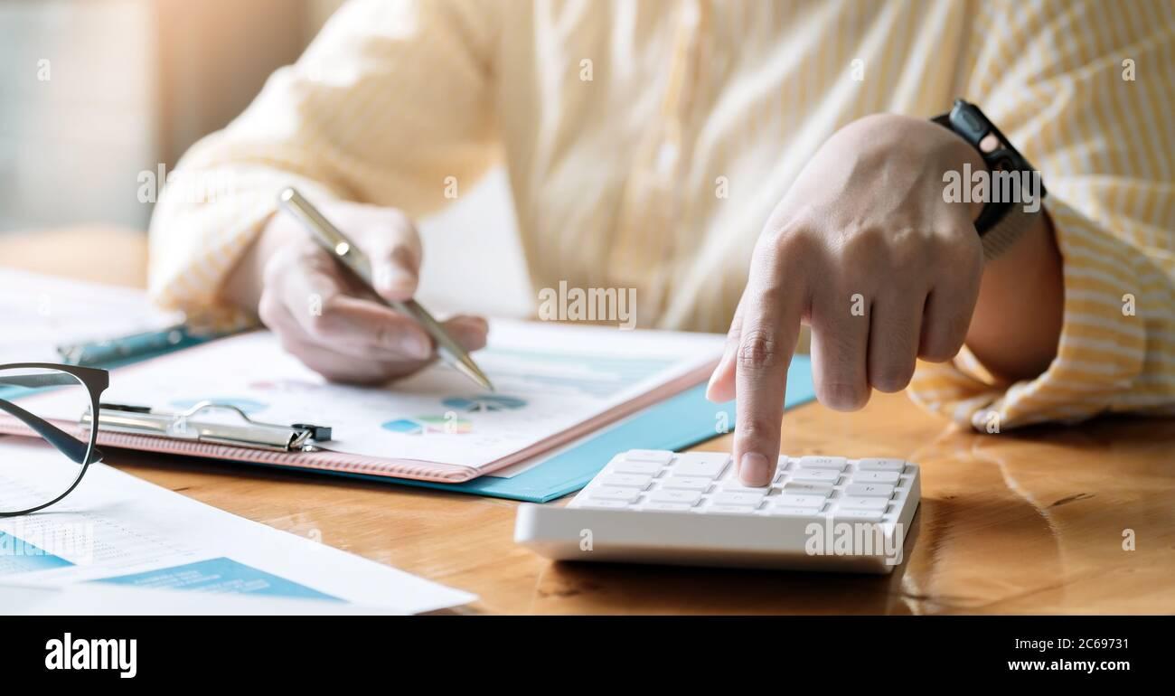 Contable o contable trabajando en el escritorio usando calculadora, concepto de finanzas de contabilidad. Foto de stock