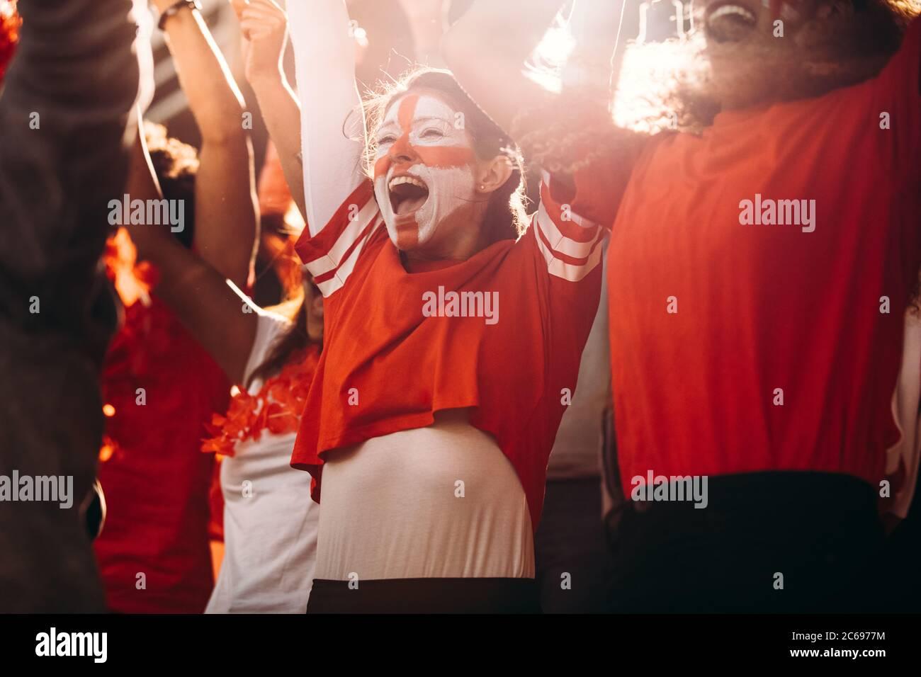 Entusiasmados aficionados al fútbol de Inglaterra celebrando en stands. Los seguidores del fútbol inglés animan a un gol en el estadio. Foto de stock