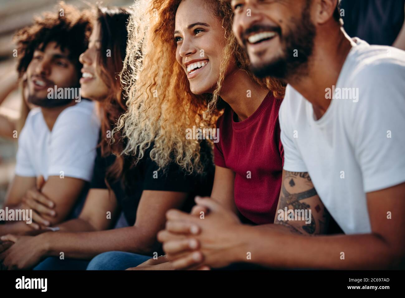 Pareja joven viendo un evento deportivo en el estadio. Grupo multiétnico de aficionados al deporte sentados en el estadio y viendo un partido de fútbol. Foto de stock