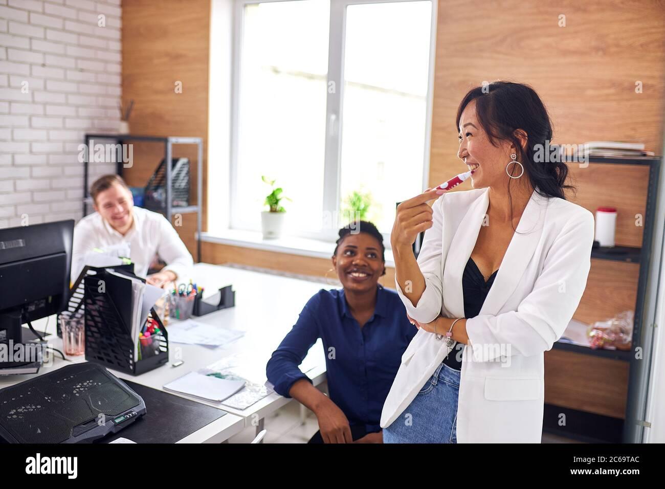 Mujer asiática alegre en camisa blanca usar rotafolios durante la presentación de su negocio, caucásicos y oyentes africanos Foto de stock
