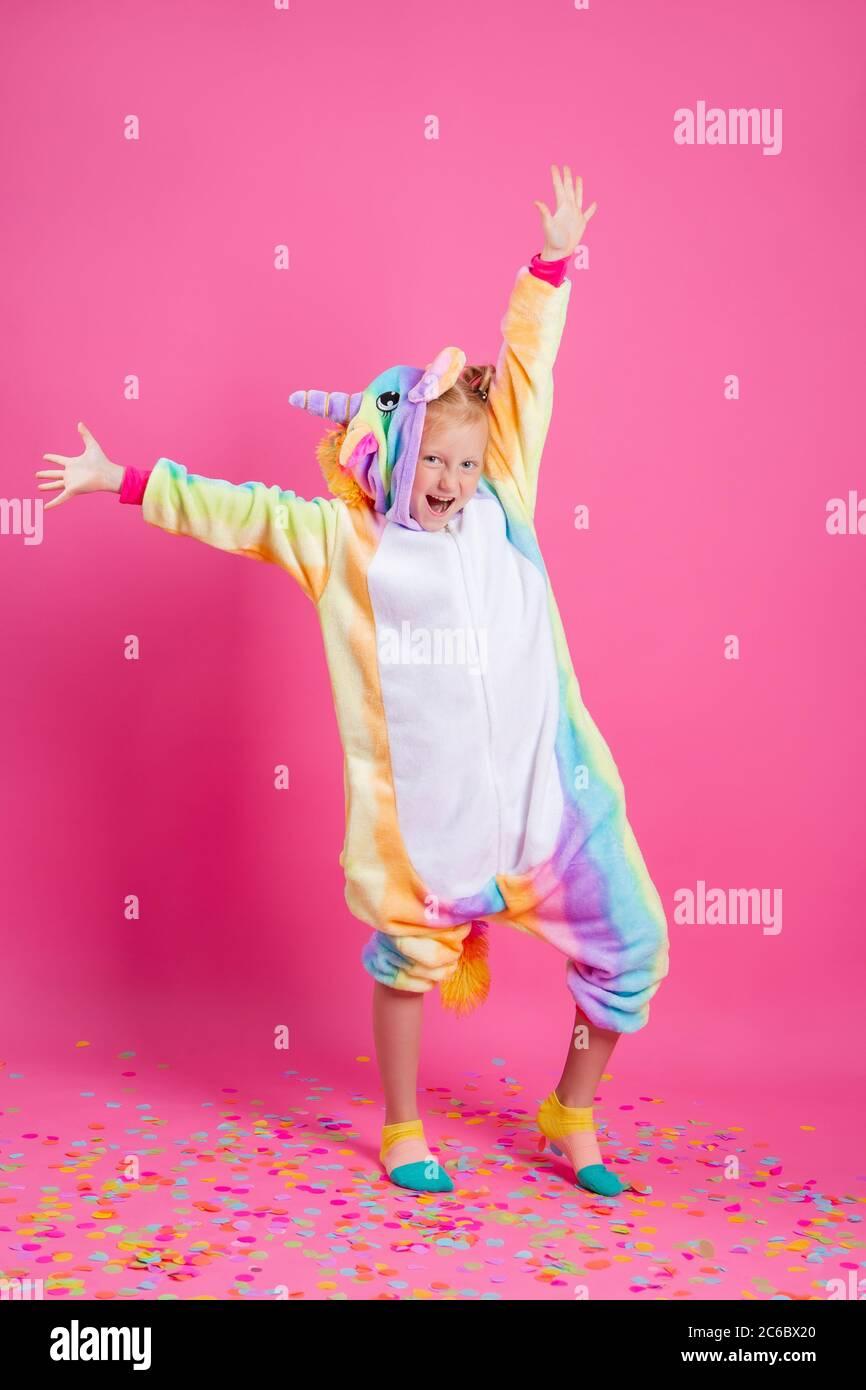 Feliz niña en kigurumi unicorn sobre un fondo rosa se regocija en confeti multicolor, espacio para el texto Foto de stock