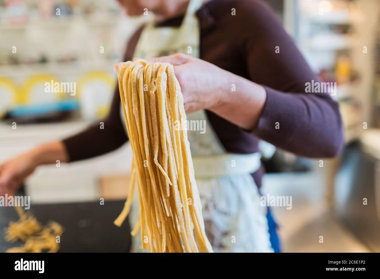 Mujer haciendo pasta casera fresca en la cocina Foto de stock
