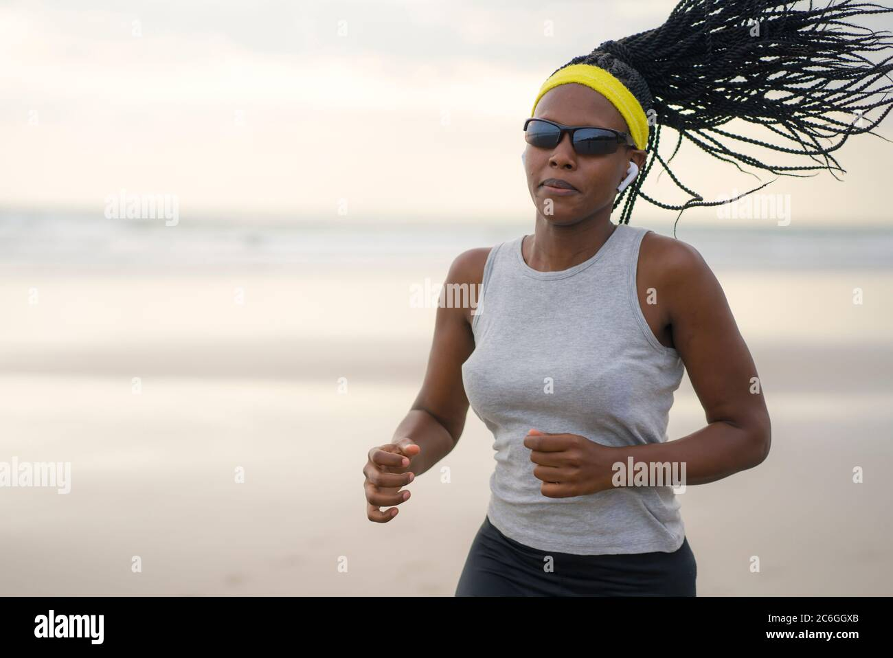 Mujer afroamericana corriendo en la playa - joven atractiva y deportiva chica negra entrenando al aire libre haciendo ejercicio de jogging en el mar en forma física Foto de stock