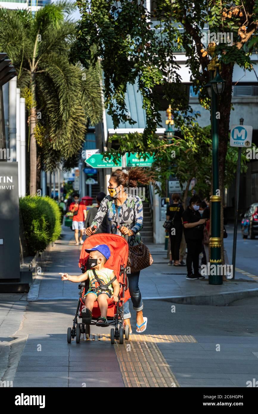Niña con máscara empujando silla de empuje con bebé durante la pandemia de Covid 19, Bangkok, Tailandia Foto de stock