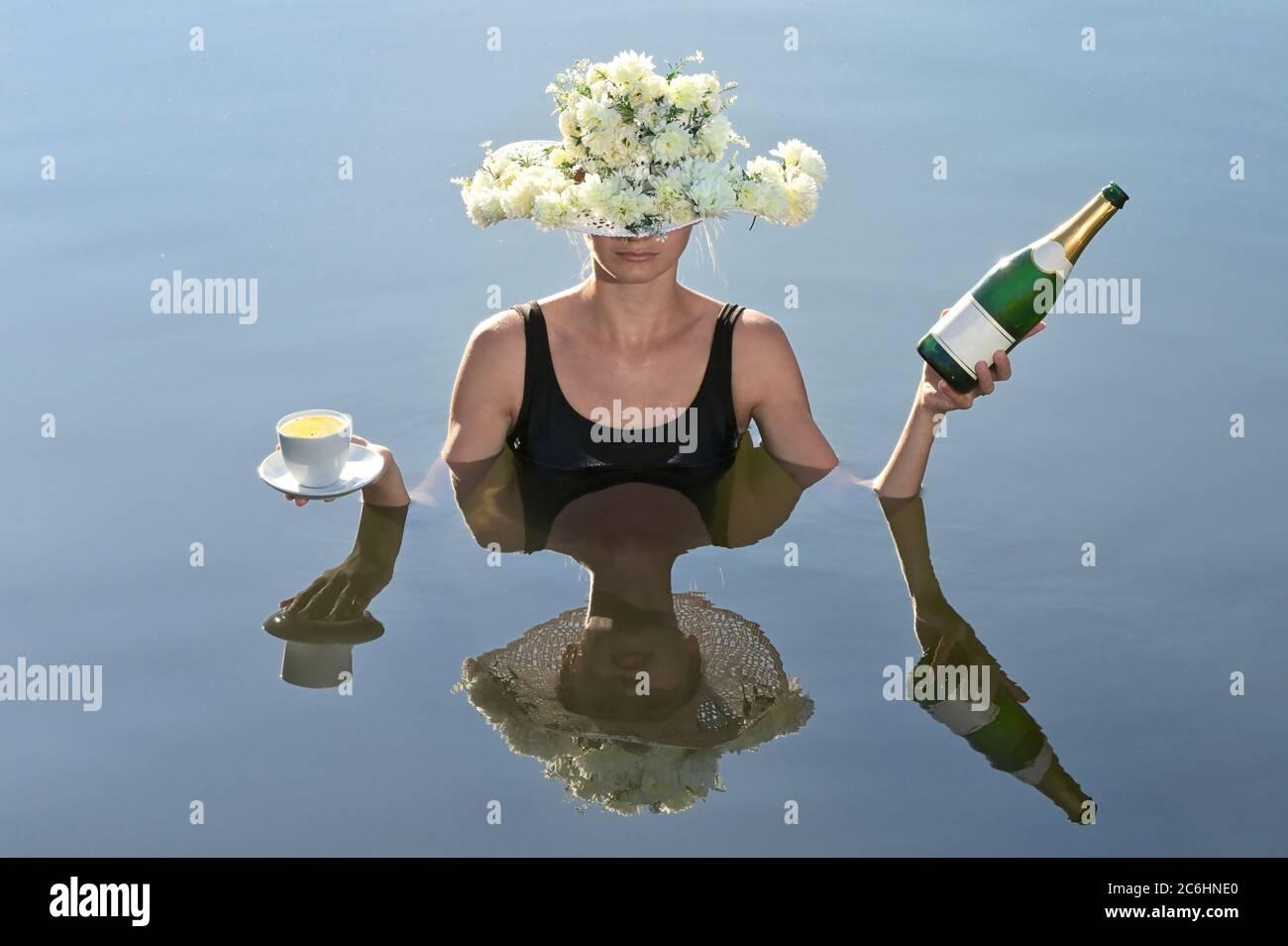 Mujer joven sirviendo una taza de café y champán Foto de stock