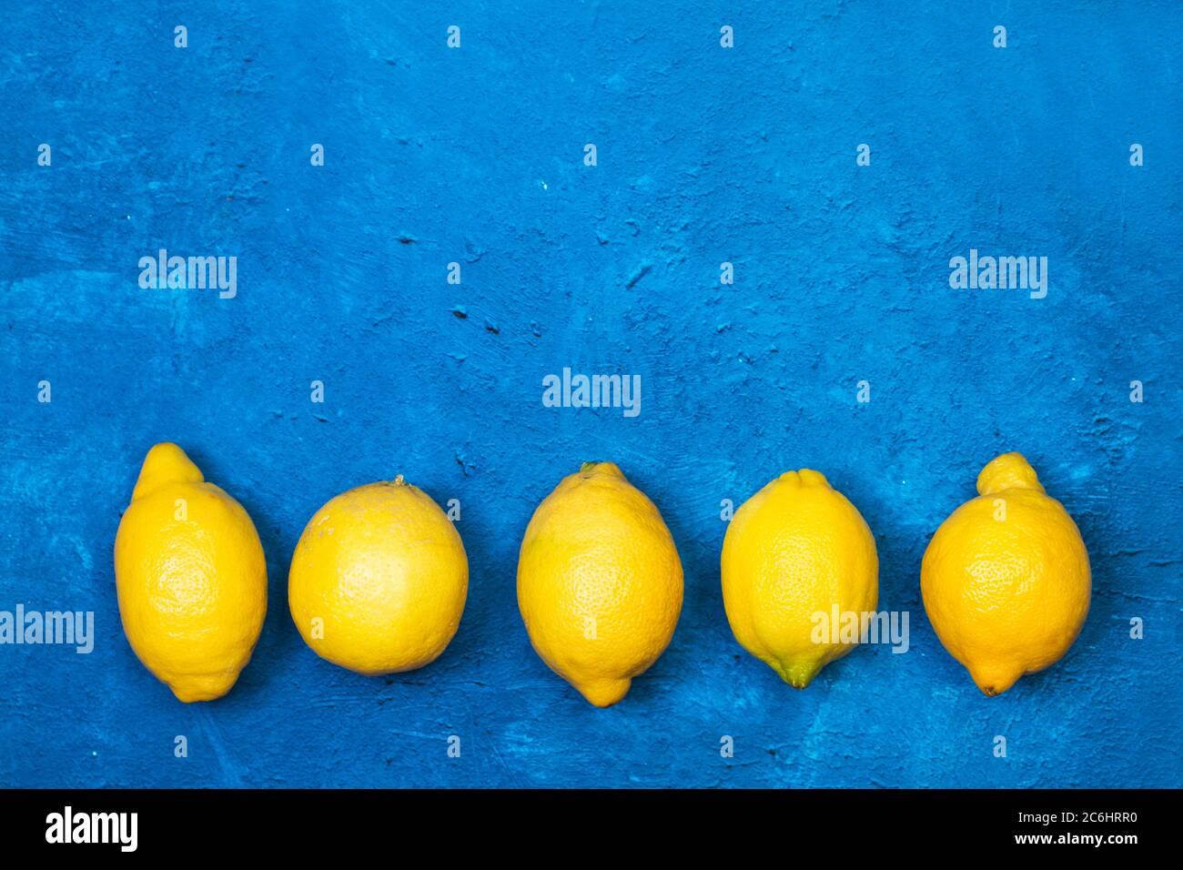 Cinco limones sobre un fondo azul clásico con textura en una vista superior Foto de stock