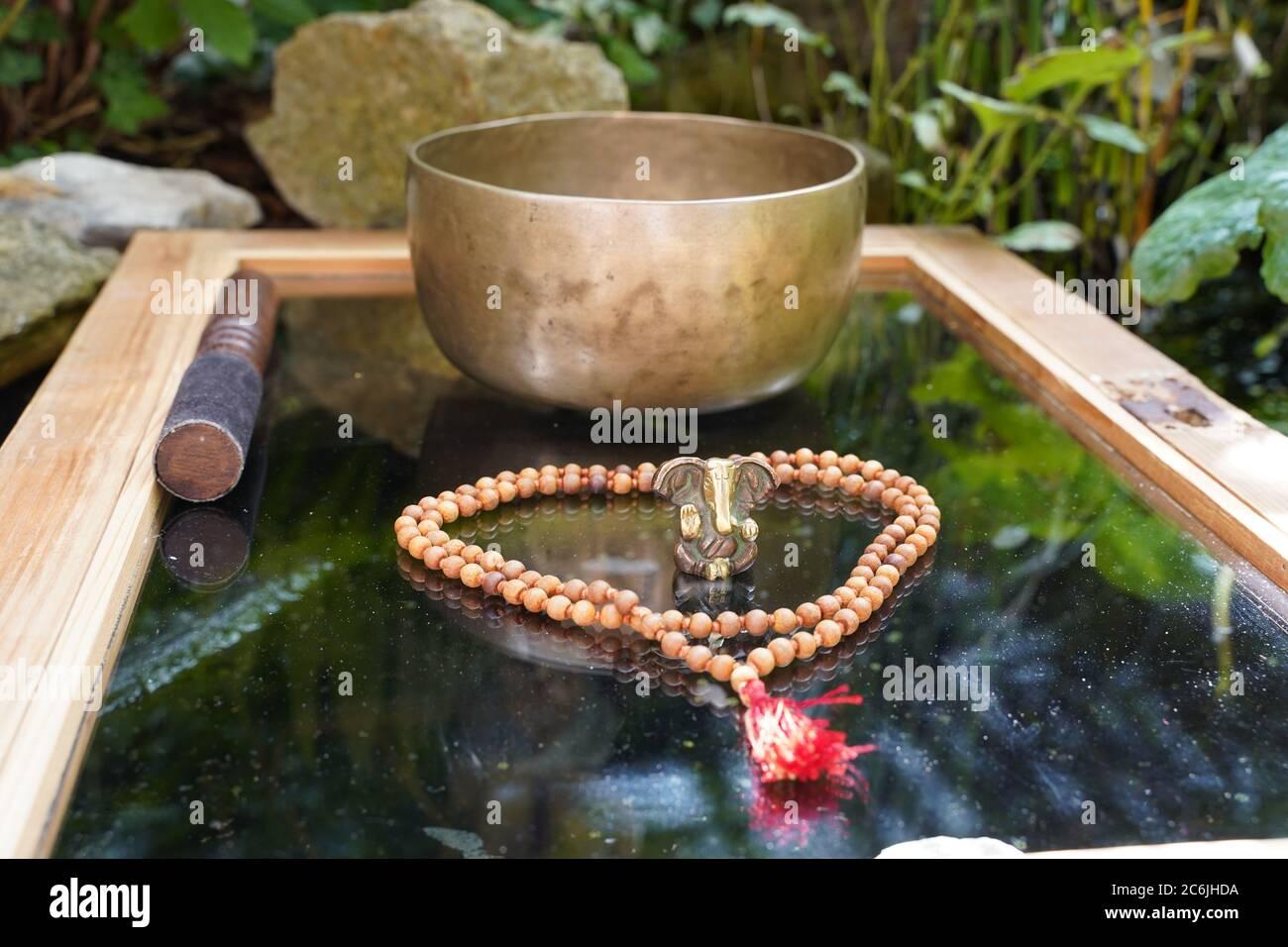 Tibetan cantando cuenco de cerca con el hermoso woodon mala y.. Ganesha Deidad para la sanación del sonido Foto de stock