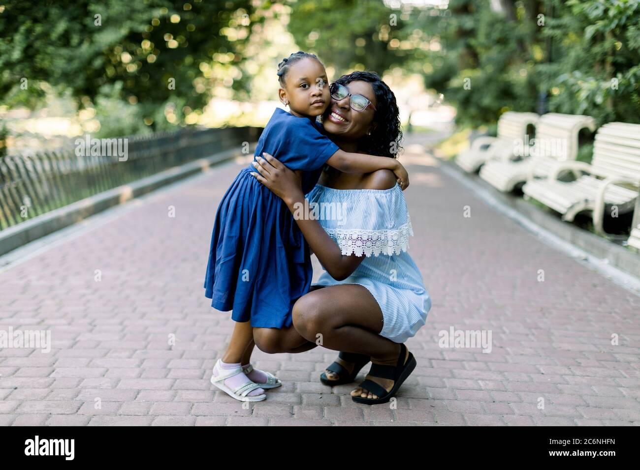 Retrato de una joven y sonriente madre africana feliz abrazando a su hija pequeña con ternura y amor en el parque. Madre y. Foto de stock
