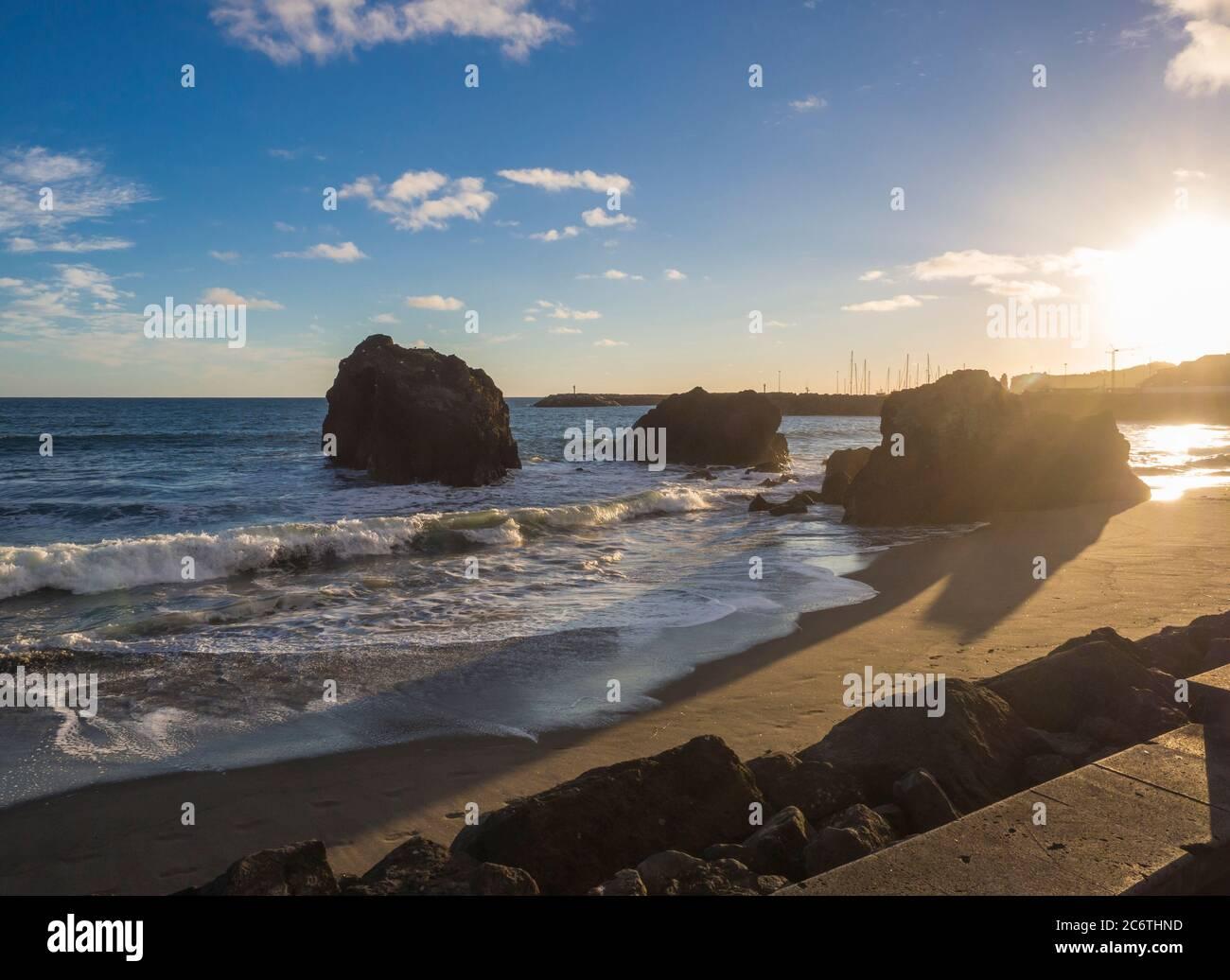 Playa de arena de la ciudad Vila Franca do campo con rocas volcánicas en el océano, cielo azul y nubes blancas, Sao Miguel, Azores, Portugal Foto de stock