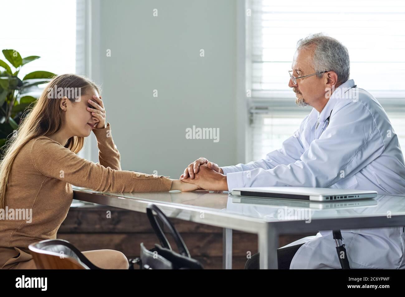 Una mujer joven llora al oír un diagnóstico desfavorable en una cita con el médico Foto de stock