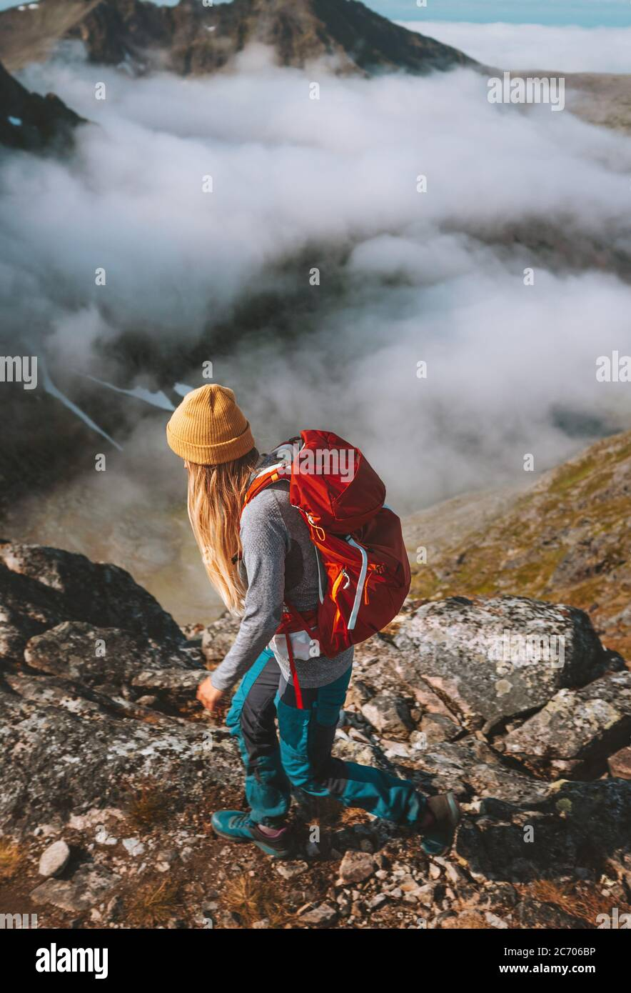 Mujer senderismo en las montañas con mochila roja viaje pista de carrera actividad vacaciones de verano estilo de vida saludable aventura al aire libre solo trekking en Noruega Foto de stock