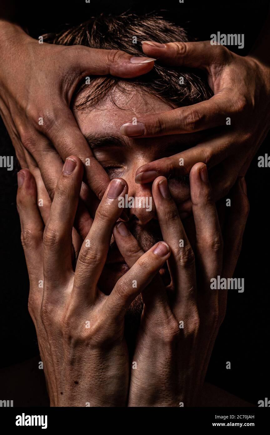 Cuatro manos cubren la cara de un hombre casi por completo. Foto de stock