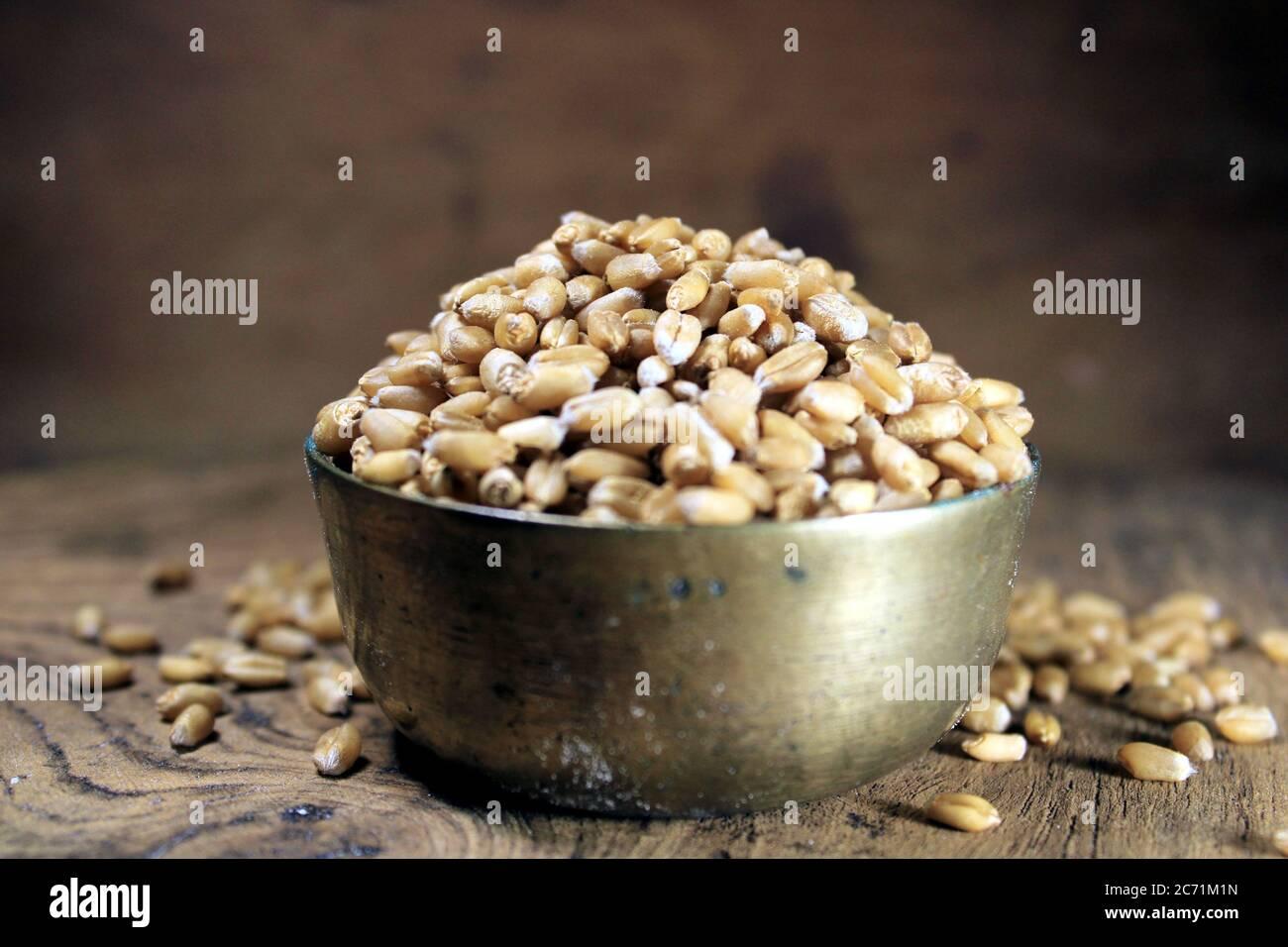 Montón de trigo orgánico de grano entero. Grano de trigo fresco cosechado en un tazón aislado sobre fondo de madera. Granos de trigo y harina de trigo. Foto de stock
