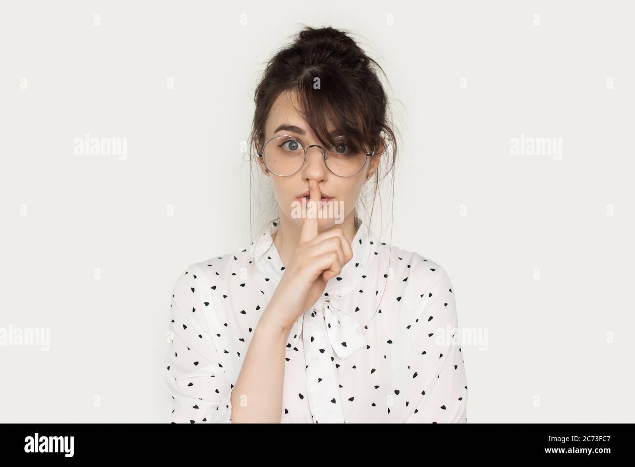 Encantadora dama morena con gafas que están gestuando el signo de silencio en una pared blanca del estudio mirando la cámara Foto de stock