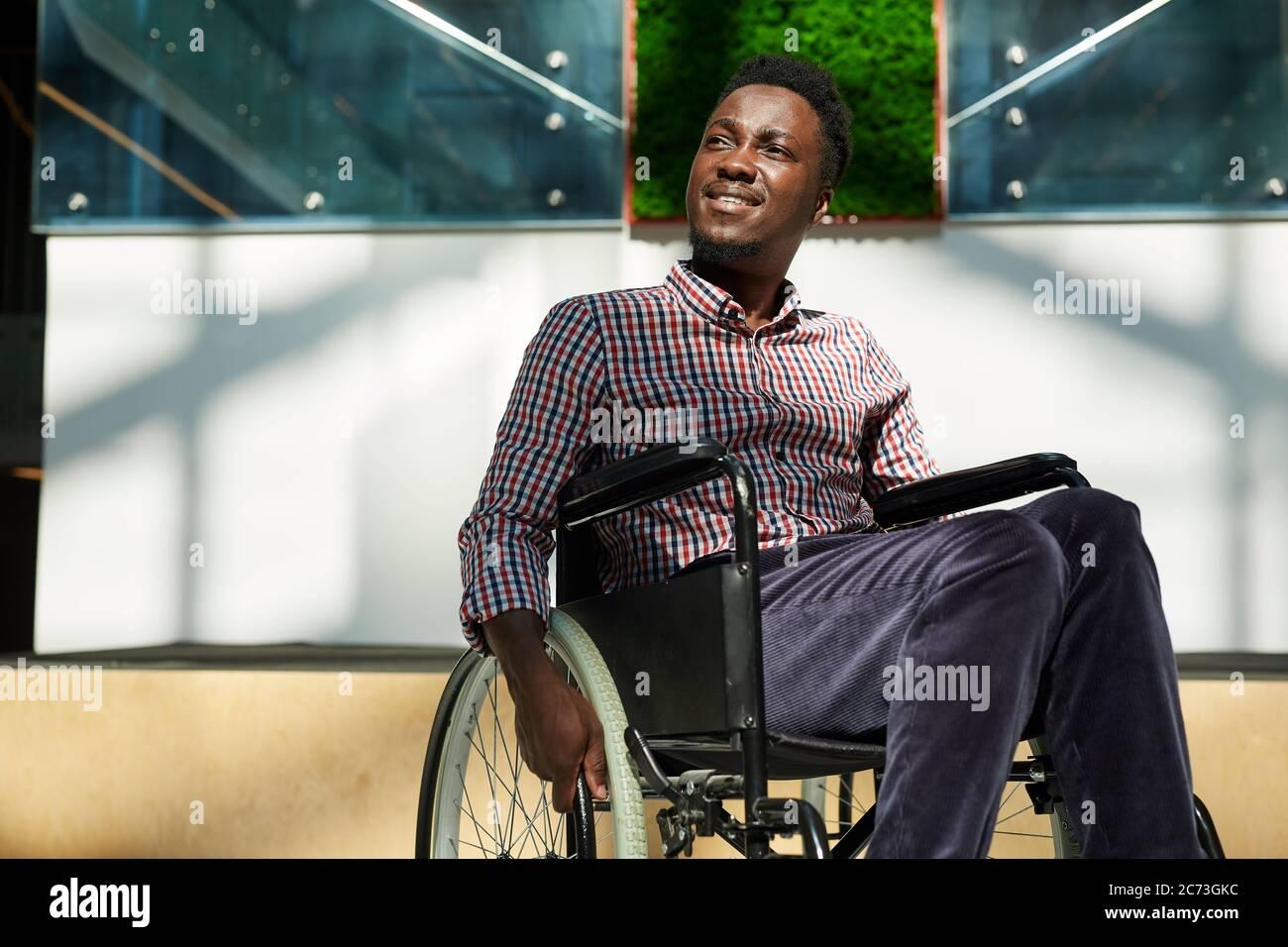 Hombre africano en silla de ruedas mirando a distancia y sonriendo en la oficina moderna Foto de stock