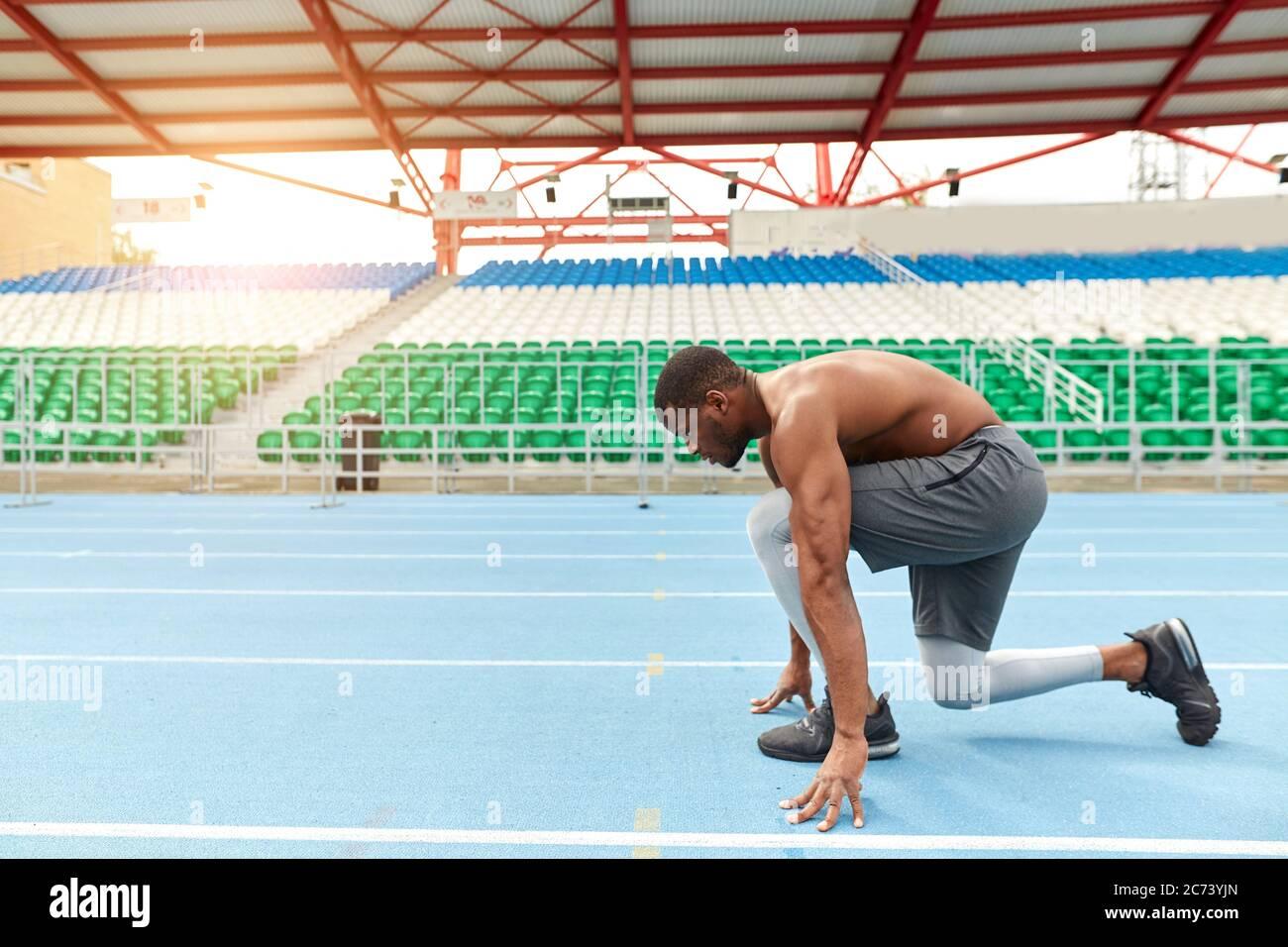 el talentoso corredor africano está listo para sprint, hombre parado en la posición de inicio bajo, foto de vista lateral completa. espacio de copia Foto de stock