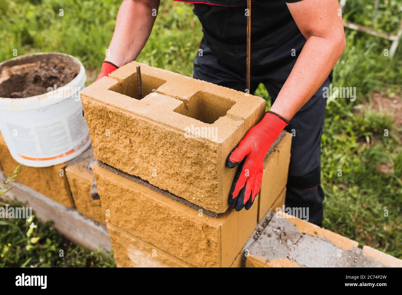 El trabajo duro de un constructor - un profesional de ladrillo hábilmente construye paredes de ladrillo y bloque de concreto Foto de stock