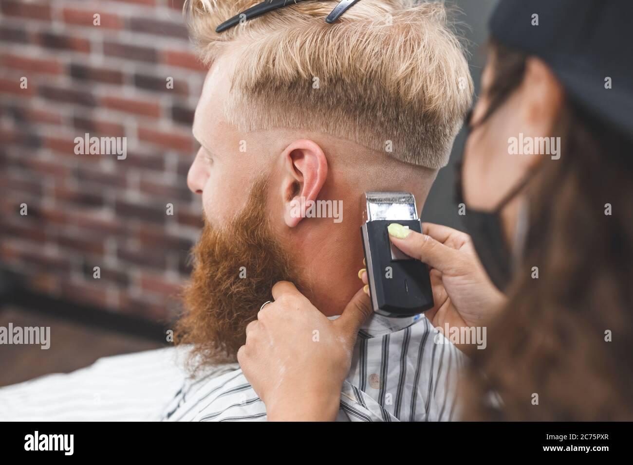 El hombre está cortando el pelo en una peluquería. Cuidado del cabello. Barbería en máscara de protección contra virus. Corte de pelo en cuarentena Foto de stock
