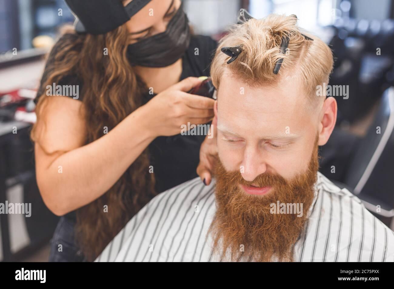 Corte de pelo para hombre en una peluquería. Cuidado del cabello. Barbería en máscara de protección contra virus. Corte de pelo en cuarentena. Foto de stock