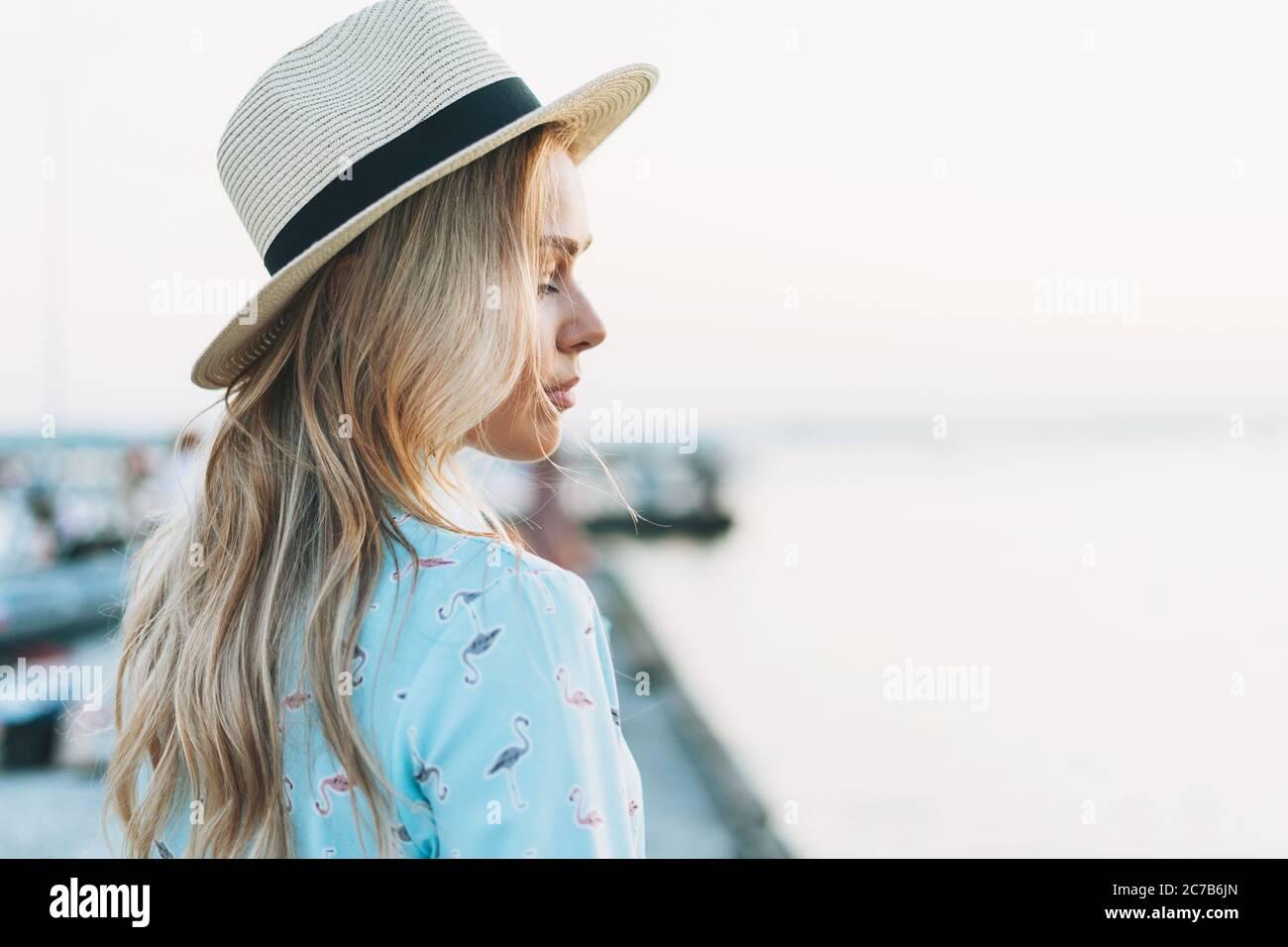 Hermosa mujer joven rubia con vestido azul y sombrero de paja en el muelle al atardecer Foto de stock