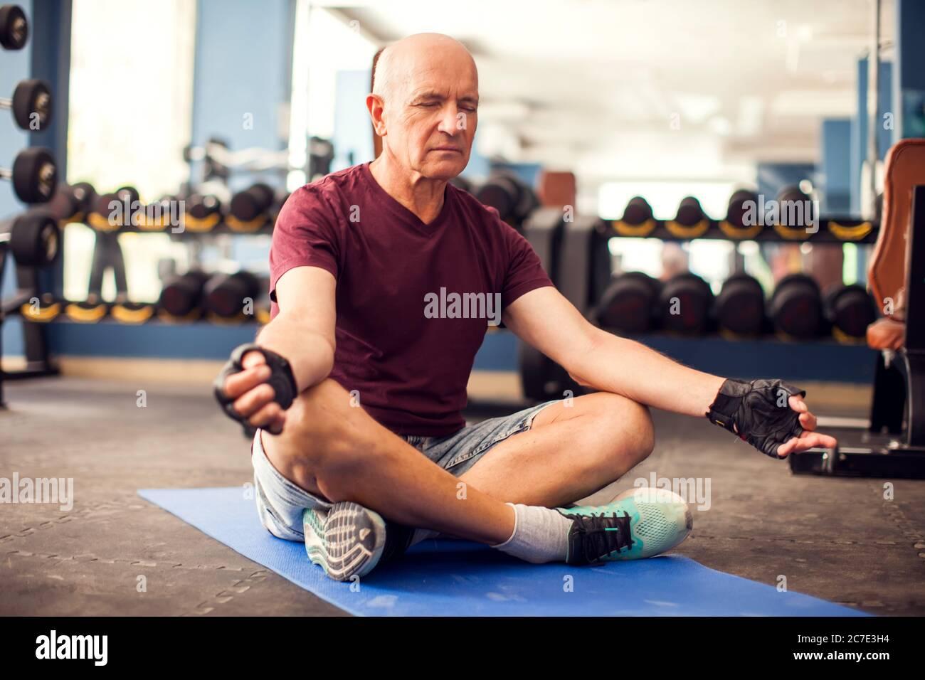 Un retrato de un hombre mayor calvo haciendo ejercicio de relajación en el gimnasio. Personas, salud y estilo de vida Foto de stock