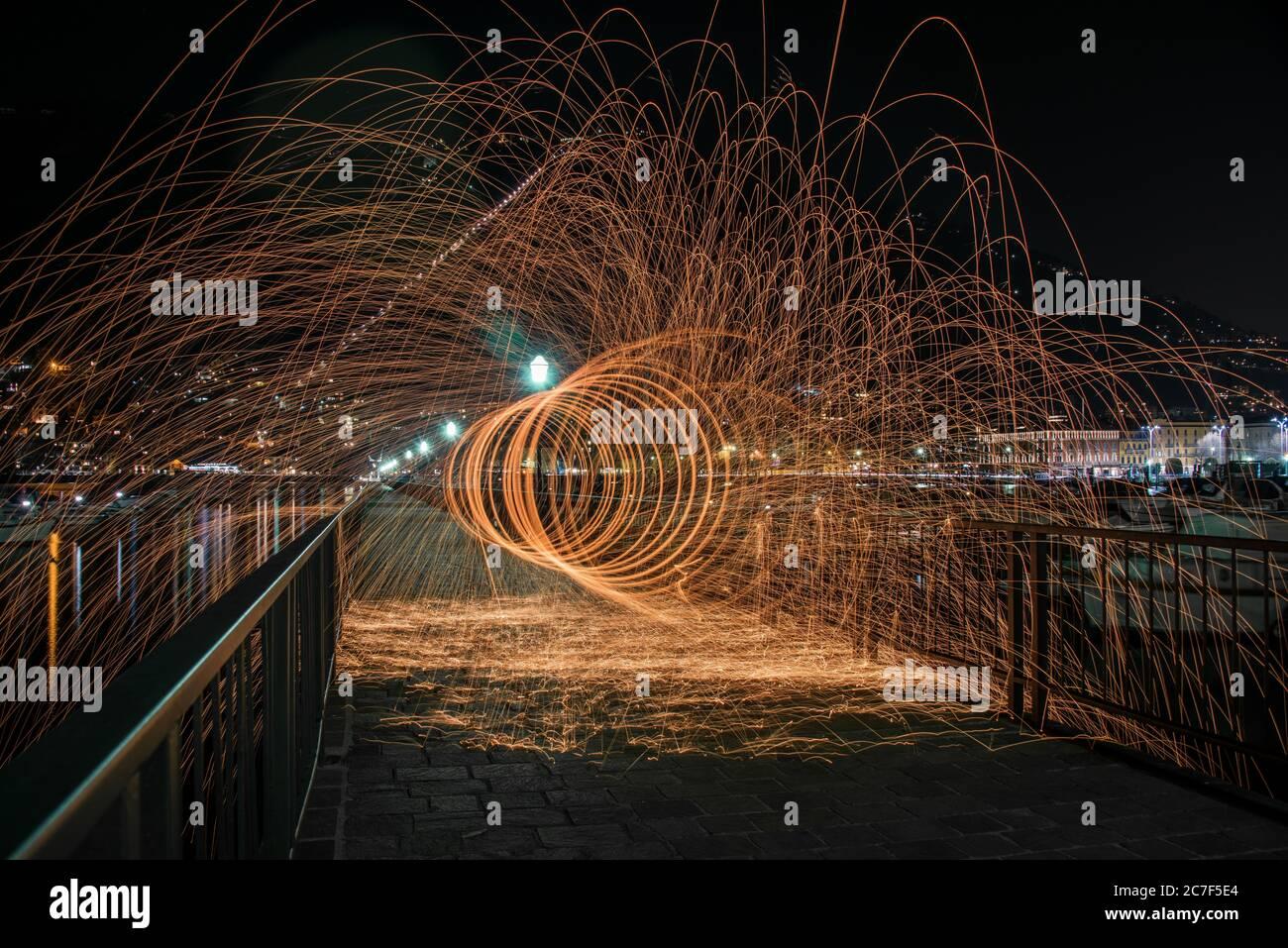 Tiro horizontal de lana de acero efecto en un puente con barandillas de metal en la noche en como, Italia Foto de stock