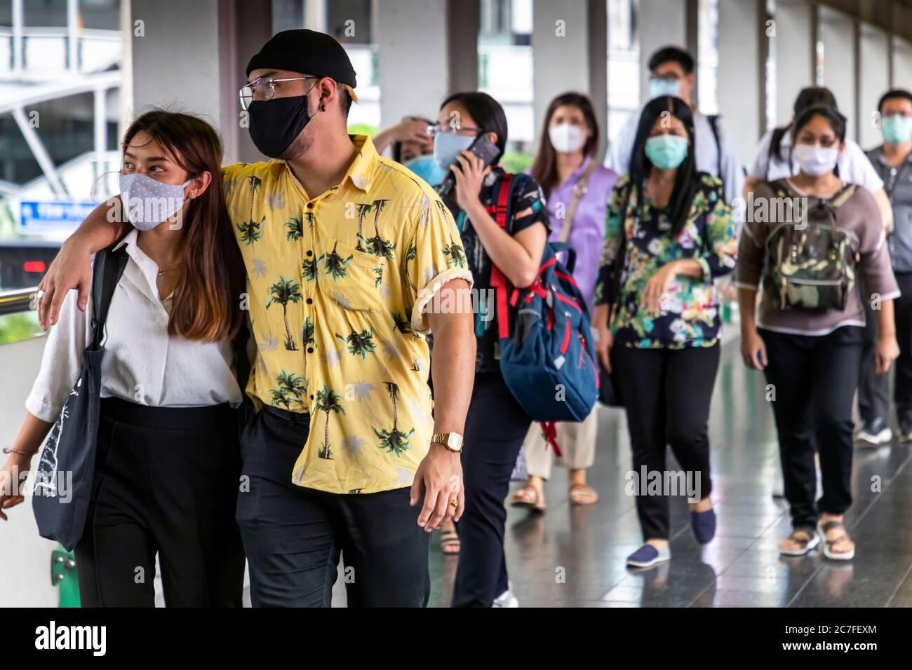 Pareja y peatones que usan máscaras durante la pandemia de Covid 19, Bangkok, Tailandia Foto de stock