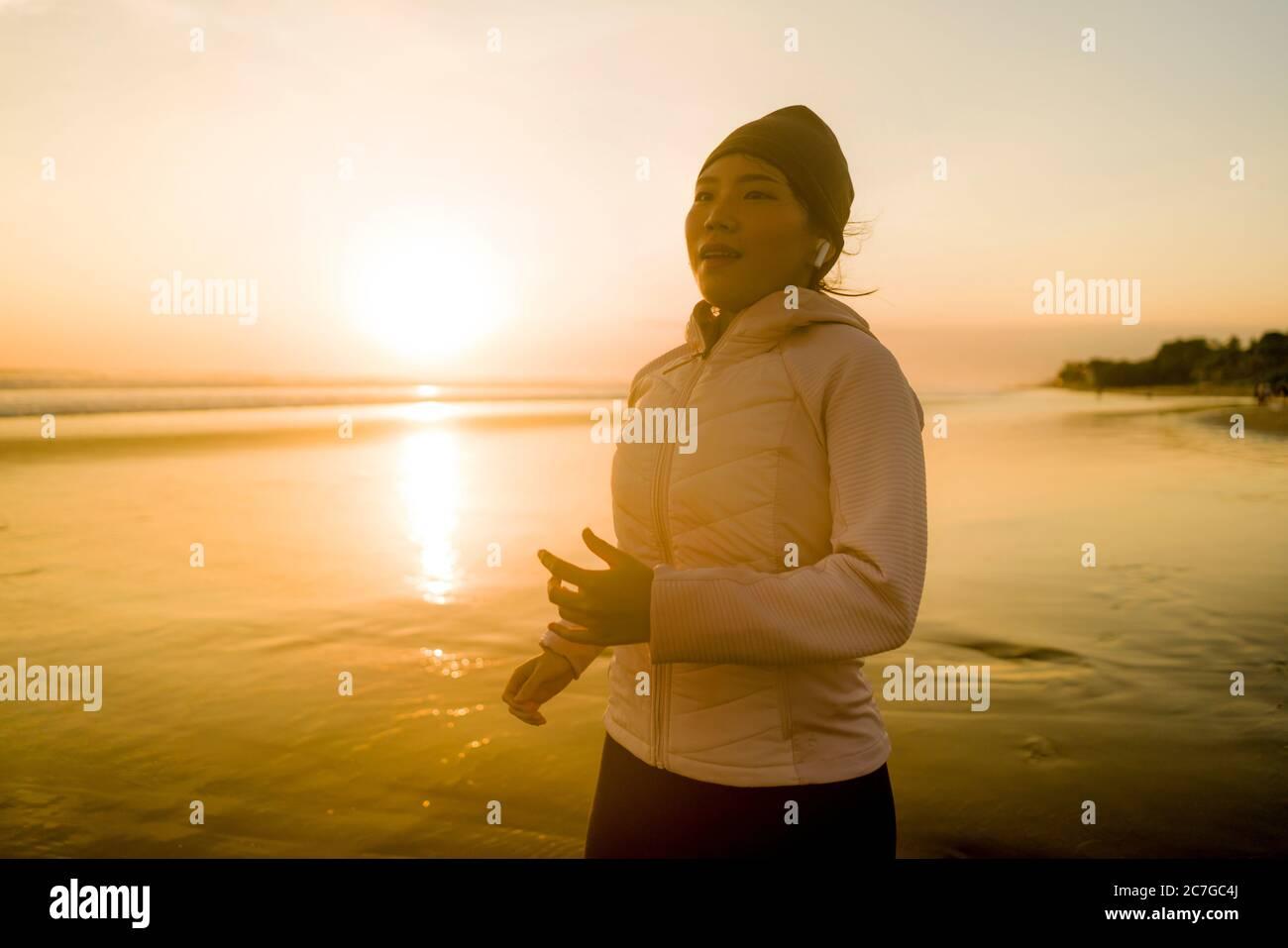 Chica asiática corriendo en la playa - joven atractiva y feliz China haciendo ejercicio de jogging en la hermosa playa disfrutando de la aptitud y el runas saludable Foto de stock
