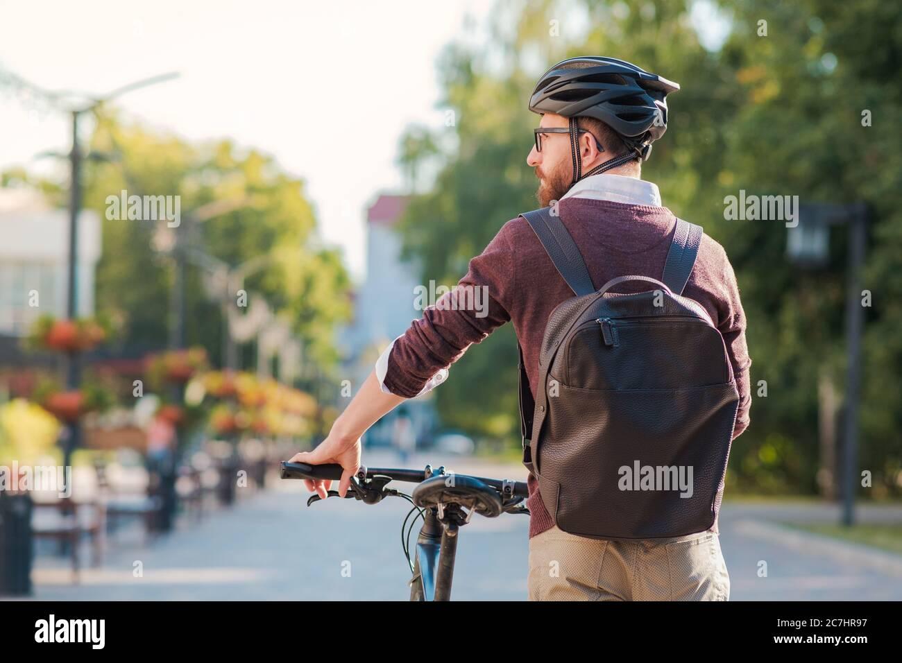Retrato de un hombre que lleva casco de bicicleta en una ciudad. Ciclismo seguro en la ciudad, desplazamientos en bicicleta, imagen de estilo de vida urbano activo Foto de stock