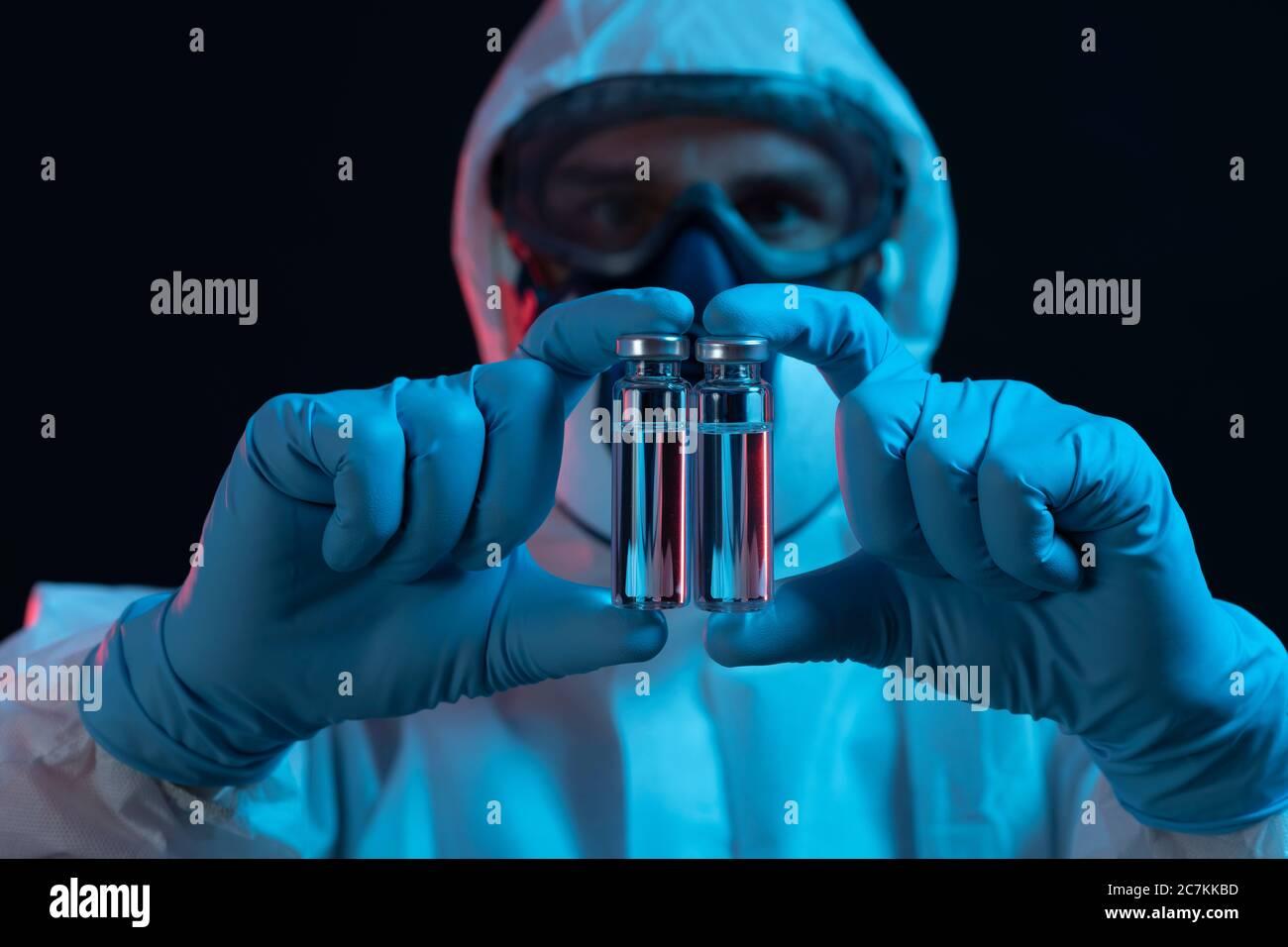 Símbolo, corona, ciencia, investigación, vacuna, peligro, distophian, traje protector, dos, viales de inyección Foto de stock