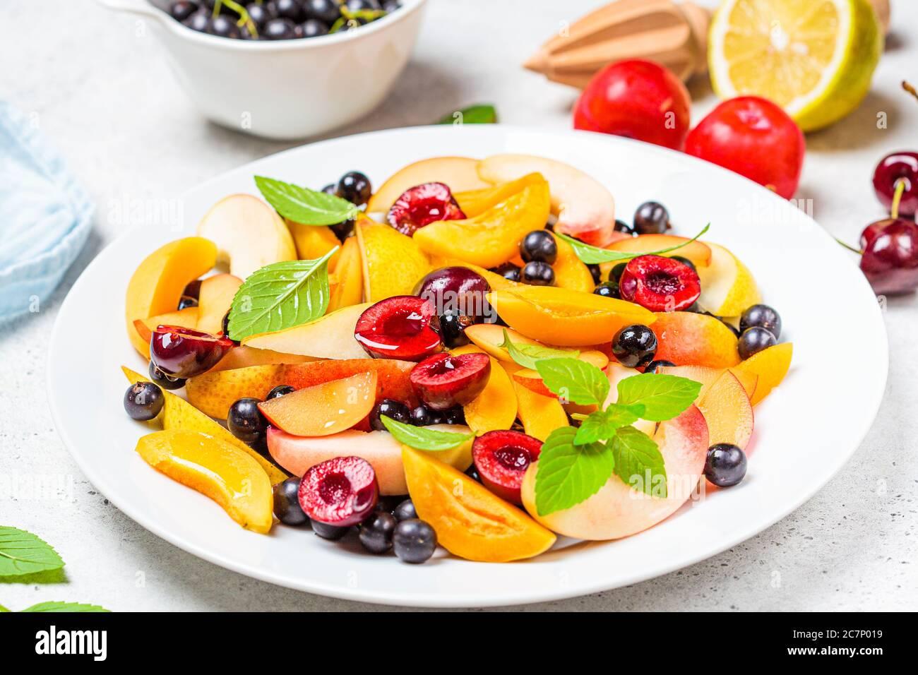 Ensalada de frutas con bayas en un plato blanco, fondo blanco. Concepto de comida vegetariana saludable. Foto de stock