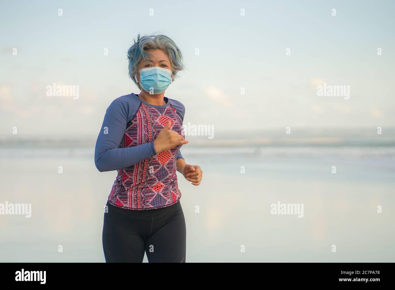 nuevo entrenamiento normal de running con máscara - atractiva y feliz mujer de mediana edad en sus 40 o 50 años haciendo footing después de la cuarentena en la hermosa playa Foto de stock