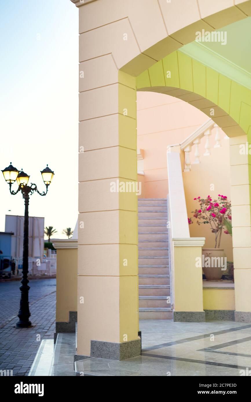 Edificio moderno del hotel con arcos arquitectónicos, escaleras y lámparas de calle cerca de la casa en un día soleado de verano, espacio de copia. Concepto de viaje de verano. Foto de stock