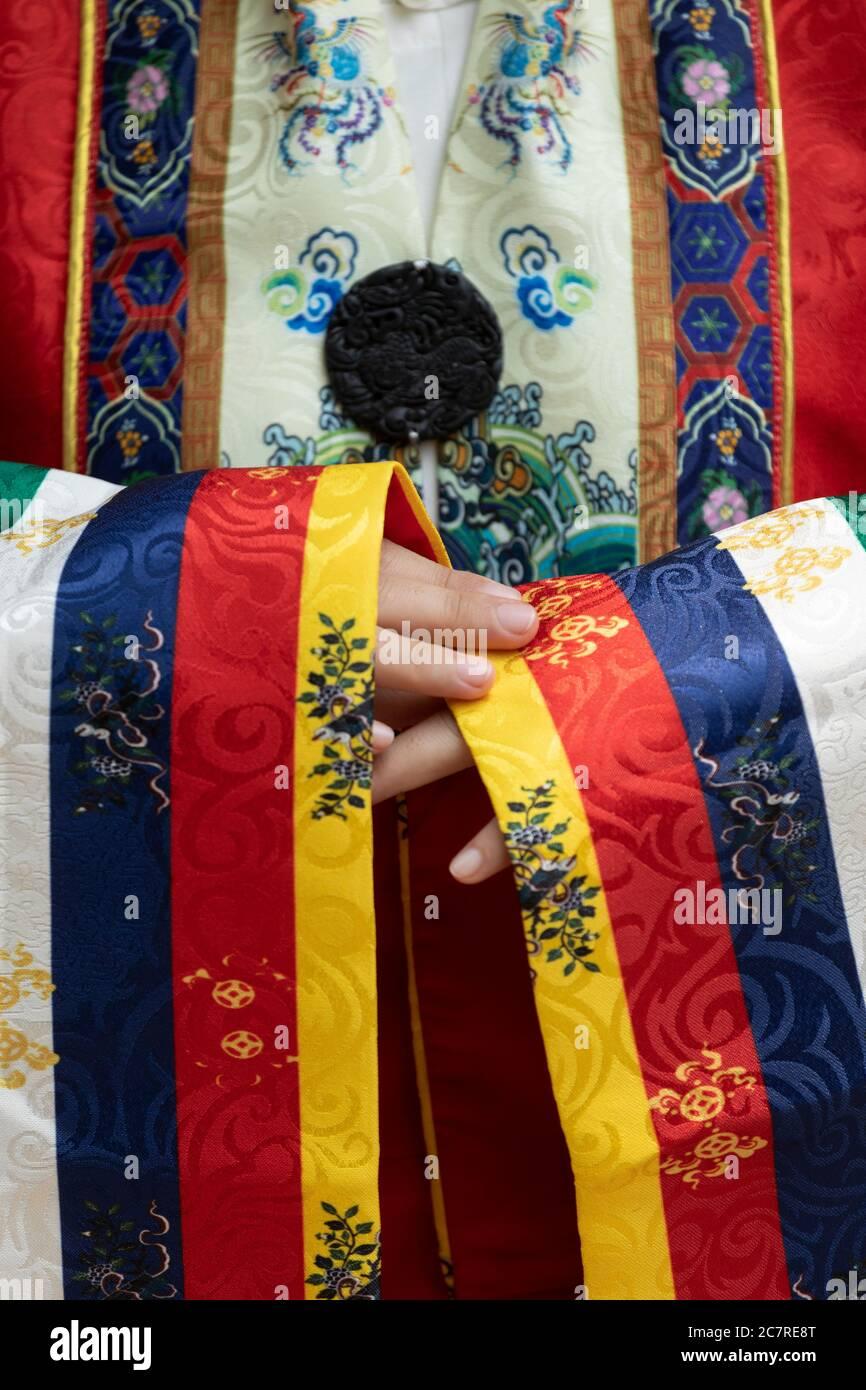 Primer plano de manos, mangas y intrincados patrones de batas de seda real tradicionales vietnamitas con colores amarillo, azul, rojo y blanco usados por la reina Foto de stock