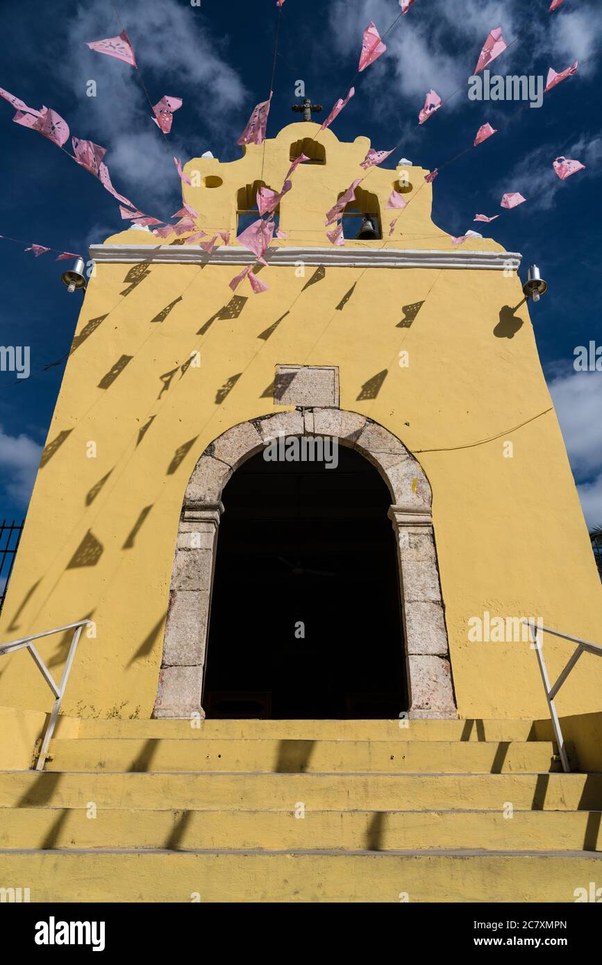 Banderas sobre la pequeña capilla colonial del siglo XVI de nuestra Señora de Guadelupe en Acanceh, Yucatán, México. Foto de stock