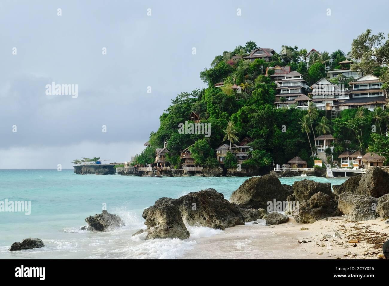 cabañas del hotel en la montaña verde del bosque cerca del mar verde. Las rocas grises, la playa de arena y las olas salpican. Un paraíso muy relajante Foto de stock