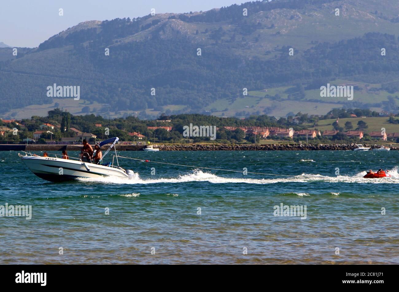 Velero de movimiento rápido remolcando gente en un anillo de goma naranja inflado en la bahía de Santander Foto de stock