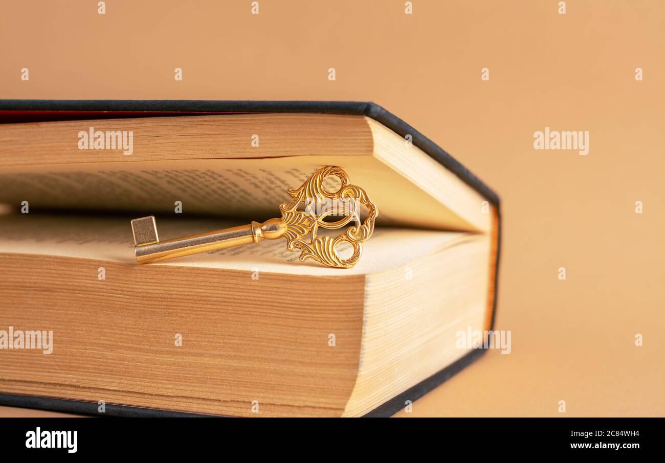 Una vieja y hermosa llave entre las páginas del libro viejo. Foto de stock