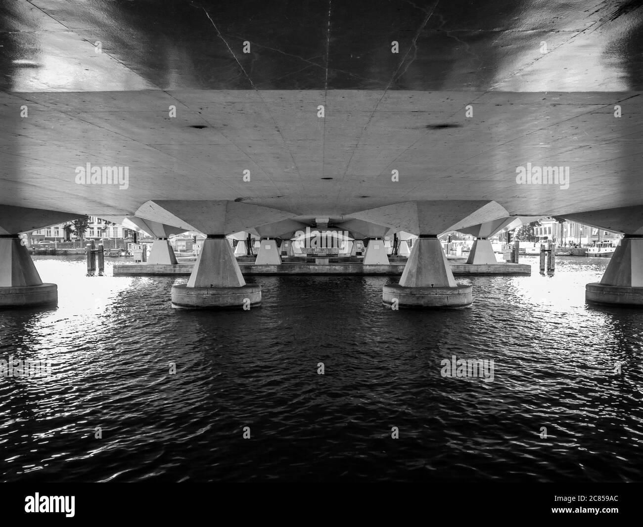 Una imagen abstracta en blanco y negro de debajo de un puente sobre el río Amstel en Amsterdam Foto de stock