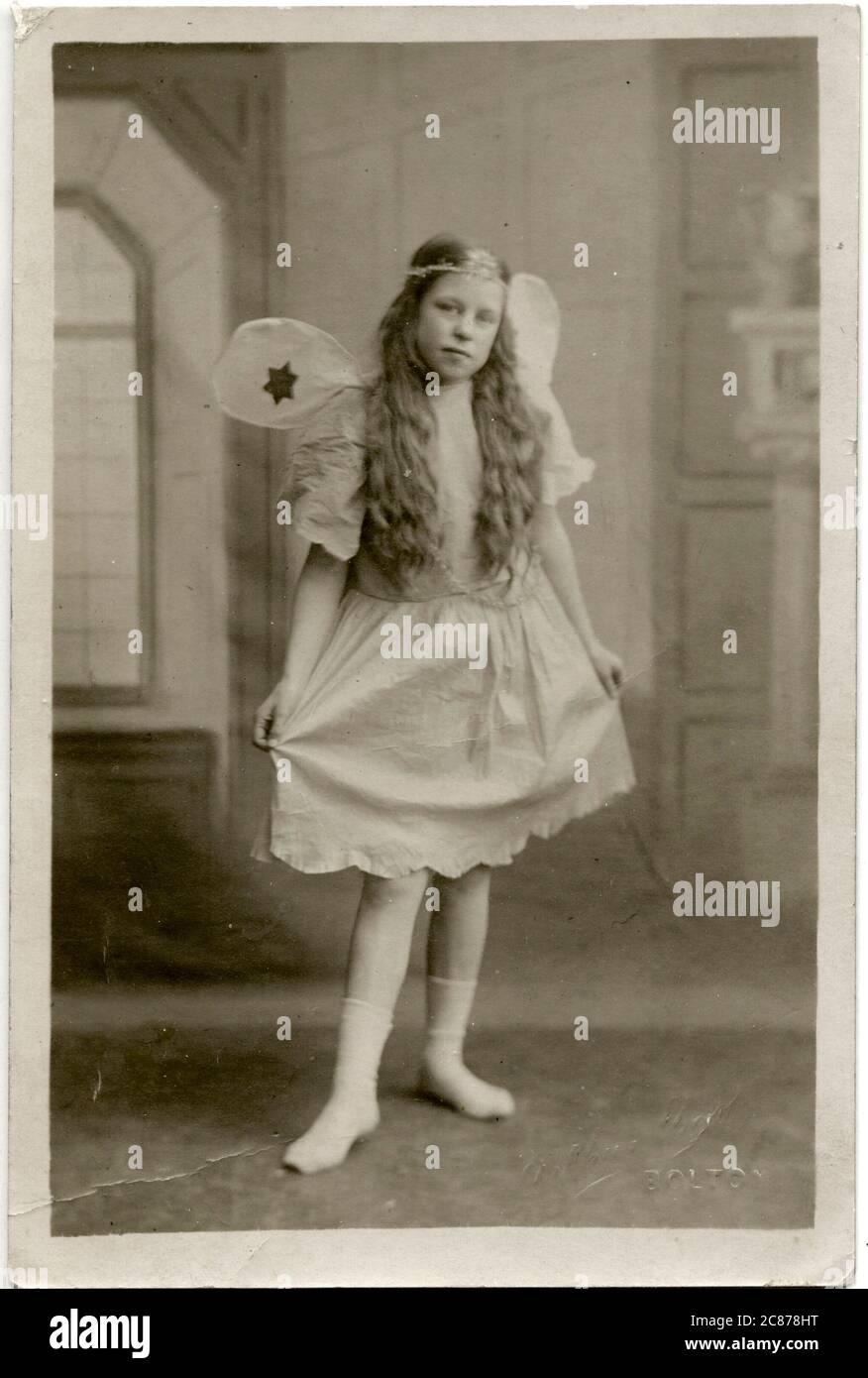 Una niña llamada Maggie en vestido de lujo, con un traje de hada en Pancake Martes 1921. Fecha: 1921 Foto de stock
