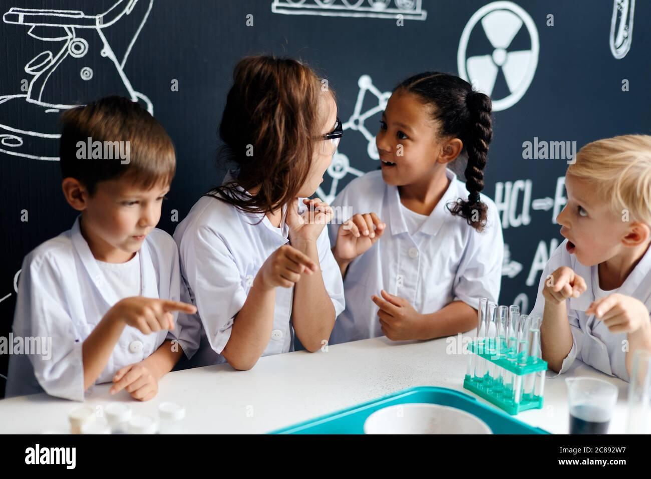 Grupo de niños multirraciales diversos en ropa blanca científica haciendo experimentos científicos con reactivos en el laboratorio, sorprendiéndose y asombrándose Foto de stock