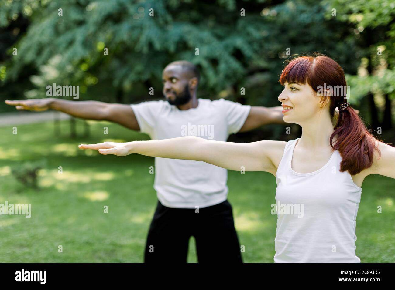 Concepto de un estilo de vida familiar saludable y yoga en el parque. Jóvenes parejas multiétnicas ejercitando al aire libre con los brazos estirados, mirando hacia adelante. Céntrese en Foto de stock