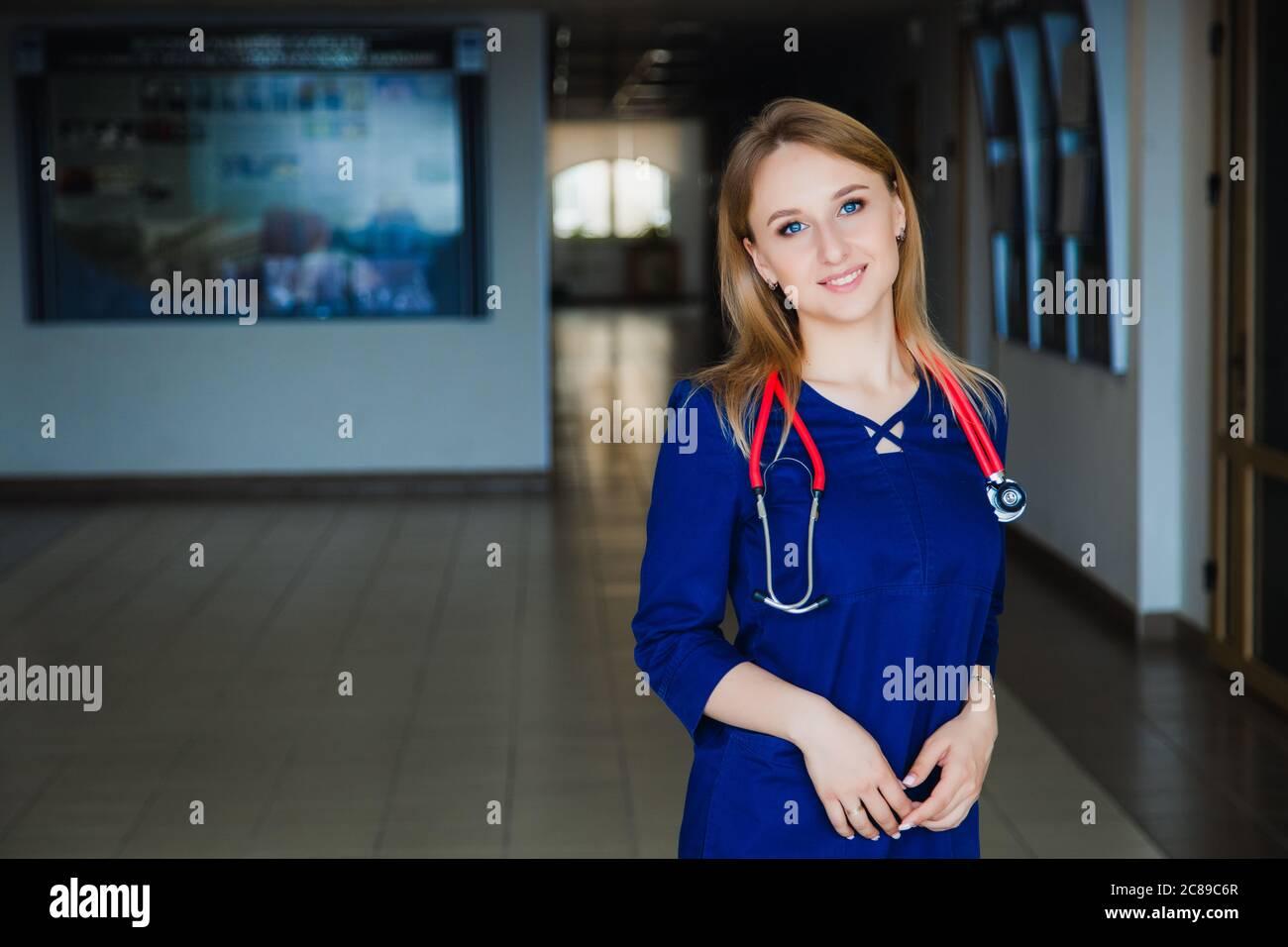Estudiante de medicina sonriendo en la cámara de la universidad en un traje azul quirúrgico. Foto de stock