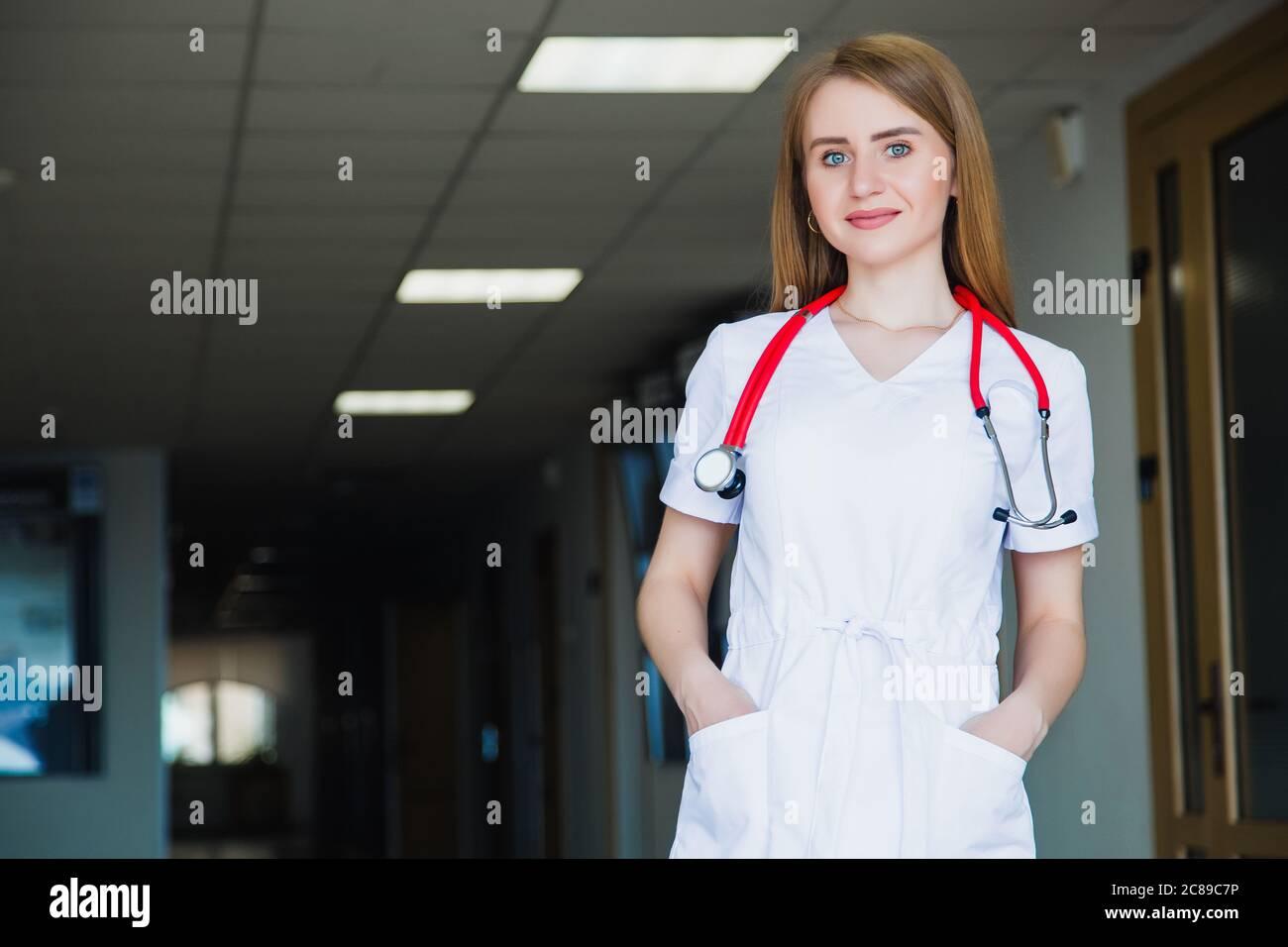 Estudiante de medicina sonriendo en la cámara de la universidad en un traje quirúrgico blanco. Foto de stock