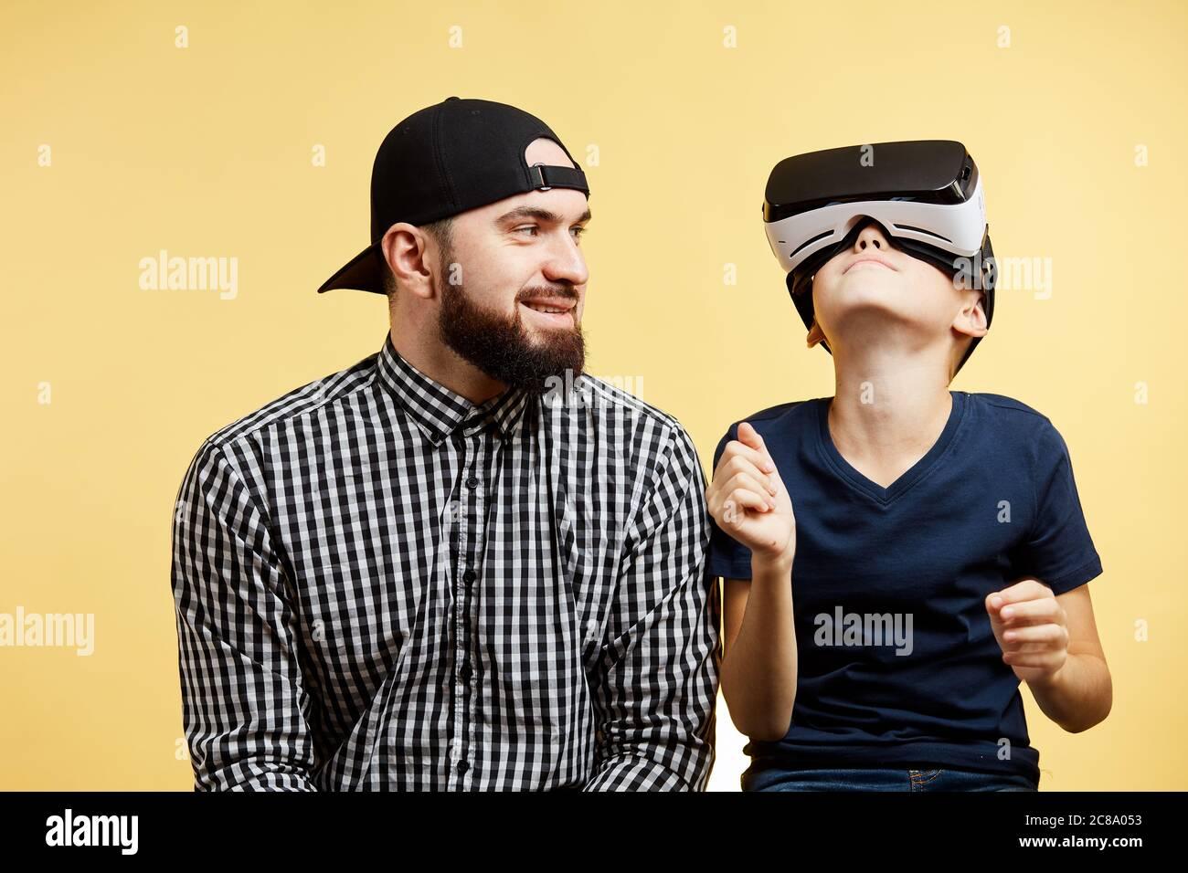 Hijo adolescente utiliza gafas de realidad virtual cerca de padre barbudo. Concepto de tecnología futura Foto de stock