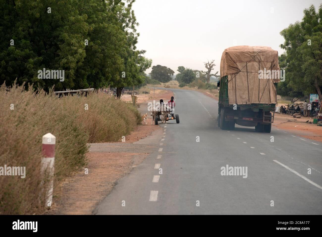 Un camión pasa un carro de burros en la región de Mopti, en las zonas rurales de Malí, África Occidental. Foto de stock