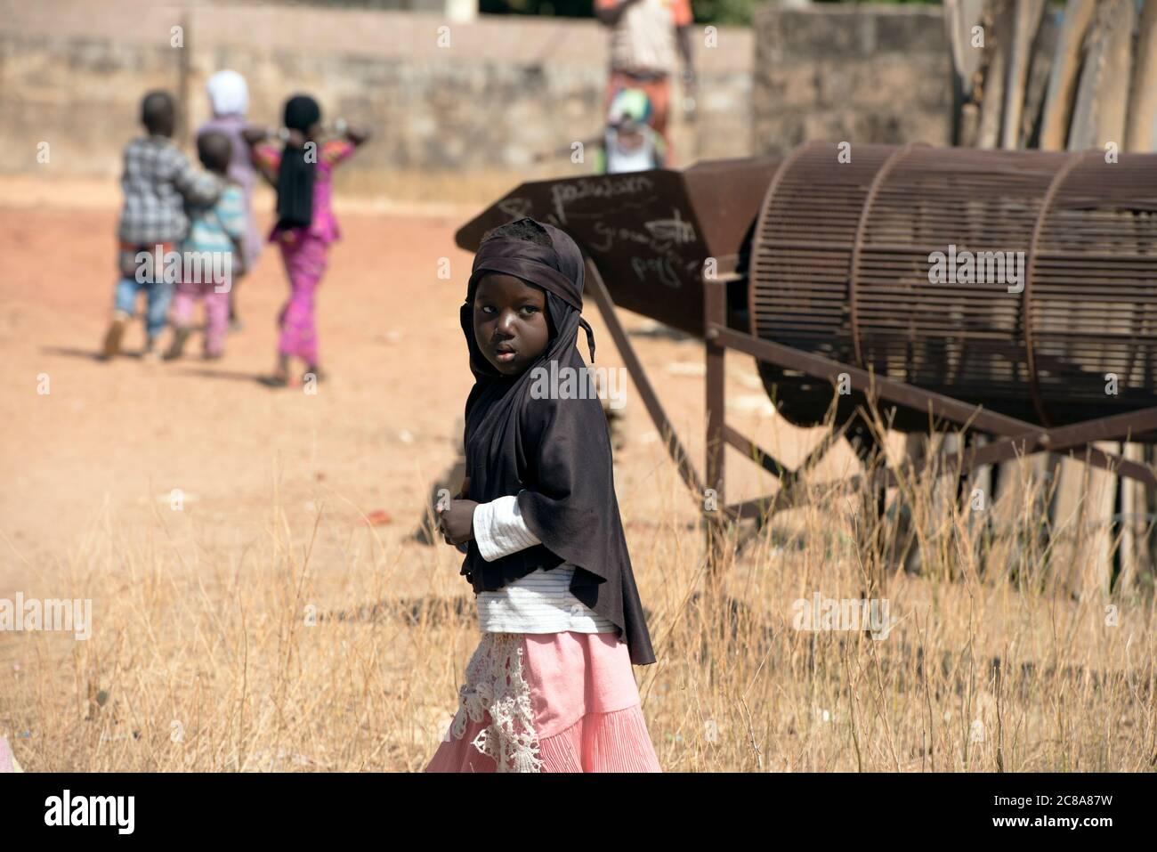 Una joven, indígena mandingo (mandinka) niña que camina de la escuela en su aldea, Gambia, África Occidental. Foto de stock